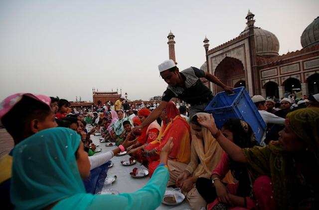 <p>A Muslim man distributes free iftar (breaking of fast) meals as charity on the first day of Ramadan at the Jama Masjid (Grand Mosque) in the old quarters of Delhi, India, May 28, 2017. (Adnan Abidi/Reuters) </p>