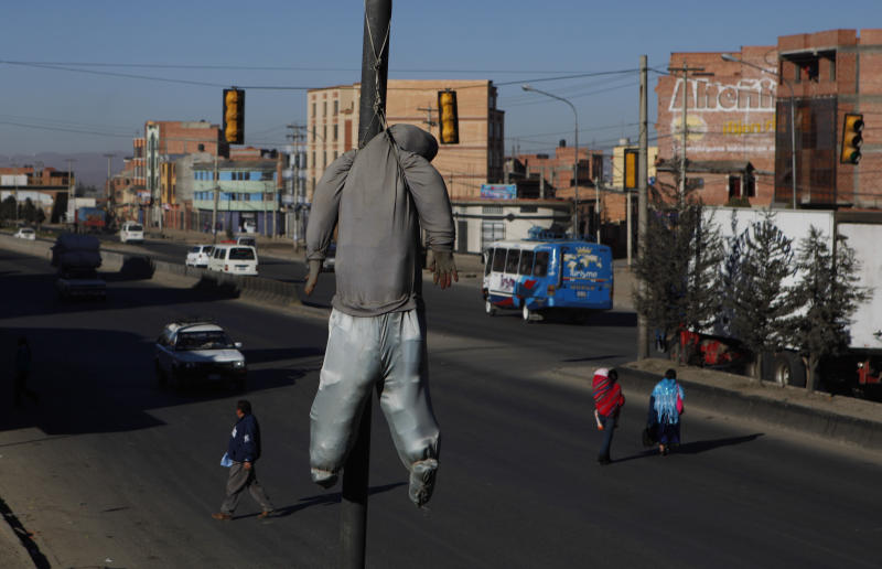 In this Aug. 18, 2013 photo, a doll hangs from a street lamp as a warning to potential criminals in El Alto, Bolivia. It's not an idle threat. At least 10 people were lynched by mobs across Bolivia in the first six months of the year, four of them in El Alto. (AP Photo/Juan Karita)