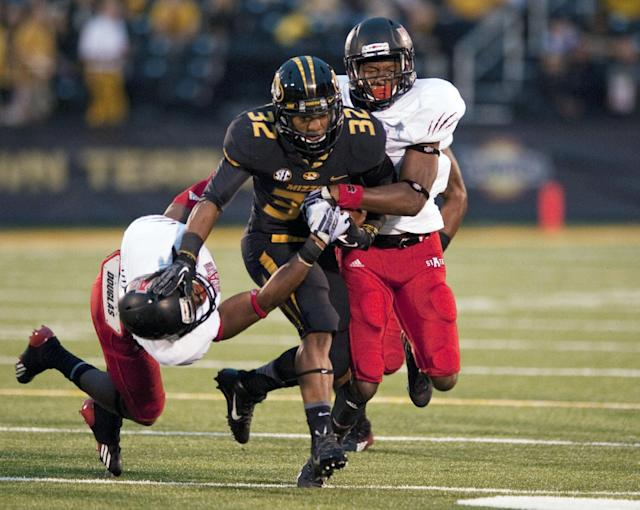 Missouri's Russell Hansbrough, center, runs past Money Hunter, left, and Sterling Young, right, during the first half of an NCAA college football game Saturday, Sept. 28, 2013, in Columbia, Mo. (AP Photo/L.G. Patterson)