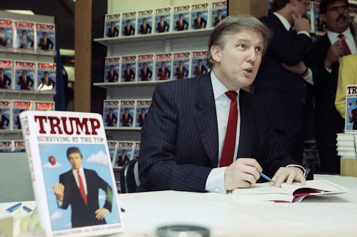 "Donald Trump signs copies of his book ""Surviving at the Top,"" written with Charles Leerhsen, in 1990. (Photo: Marty Lederhandler/AP)"