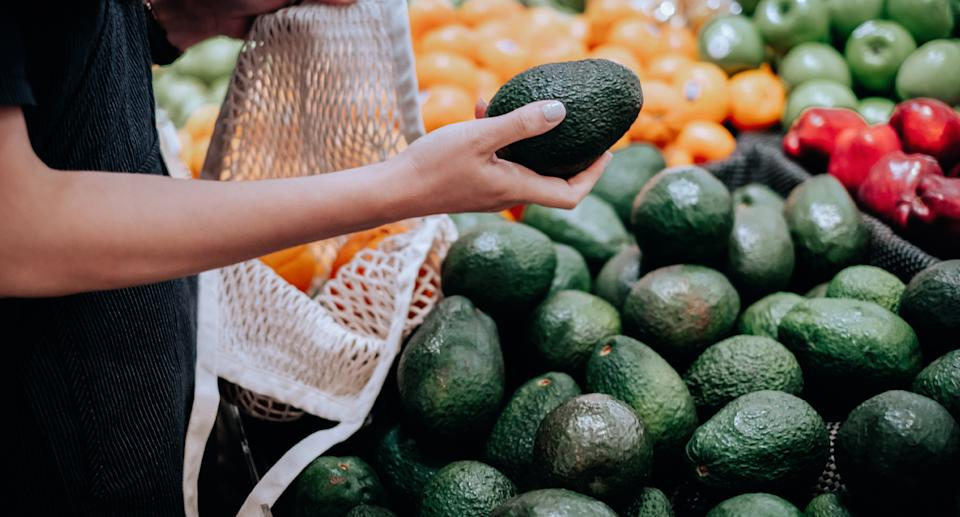 Person holds avocado in supermarket.