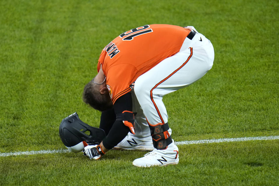 Baltimore Orioles' Trey Mancini smashes his helmet on the grass after grounding out with the bases loaded to end the eighth inning of a baseball game against the Boston Red Sox, Saturday, April 10, 2021, in Baltimore. The Red Sox won 6-4 in ten innings. (AP Photo/Julio Cortez)