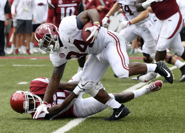 Alabama running back Damien Harris is tripped up by Arkansas Ryan Pulley in the first half of an NCAA college football game Saturday, Oct. 6, 2018, in Fayetteville, Ark. (AP Photo/Michael Woods)