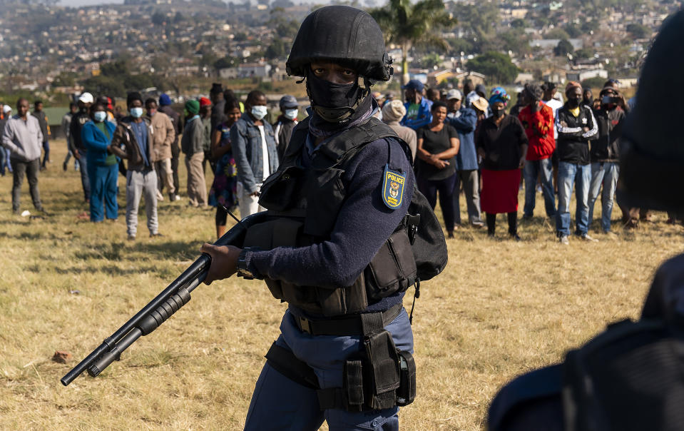 An armed policeman patrols as Police Minster Bheki Cele visits Phoenix, a neighbourhood severely affected by unrest and racial tensions near Durban, South Africa, Saturday, July 17, 2021. South African President Cyril Ramaphosa has vowed to restore order to the country after the week of violence set off by the imprisonment of former President Jacob Zuma. (AP Photo/Shiraaz Mohamed)