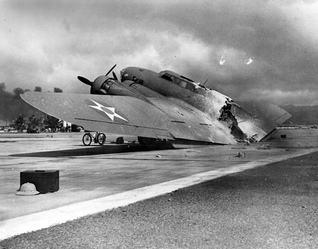 <p>A wrecked U.S. Army Air Corps B-17C bomber lies at Hickam Air Field after the Japanese raid on Pearl Harbor on Dec. 7, 1941. This plane, piloted by Capt. Raymond T. Swenson, was one of those that arrived during the raid after flying in from California. It was hit by a strafing attack after landing and burned in half. (U.S. Navy/National Archives/Handout via Reuters) </p>