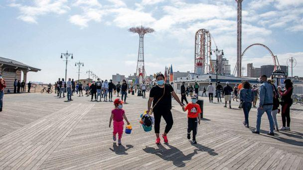 PHOTO: In this May 25, 2020, file photo, people wearing masks walk on the boardwalk at Coney Island with a view of Luna Park in the background in New York. (Alexi Rosenfeld/Getty Images, FILE)