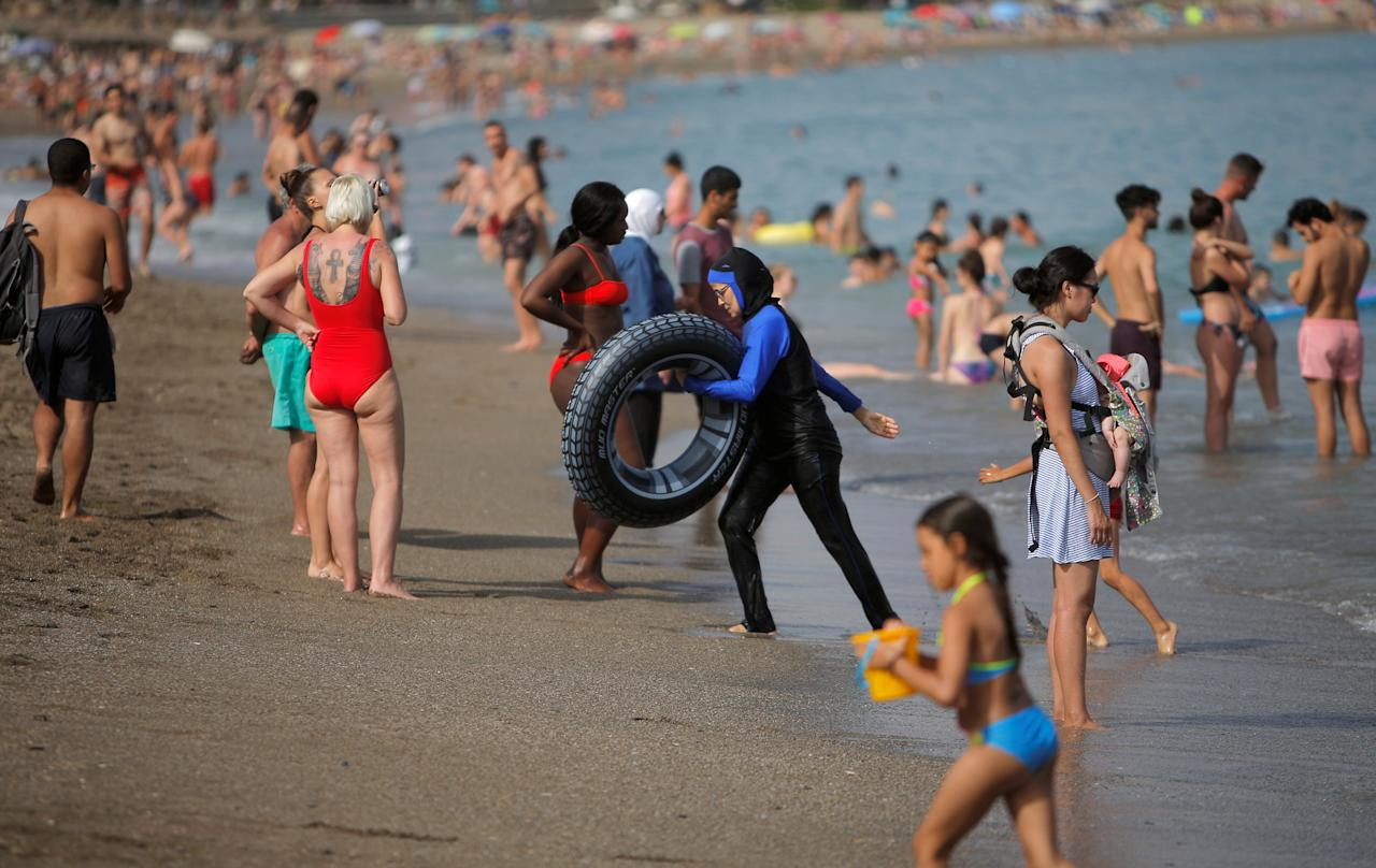 Tourists cool off on La Malagueta beach on a hot summer day during the first weekend of the summer in Malaga, southern Spain, June 24, 2018. REUTERS/Jon Nazca