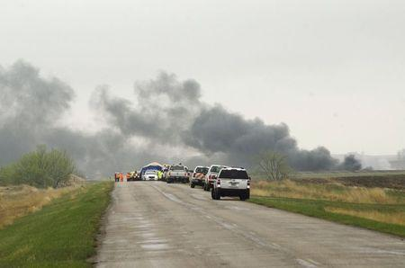 Smoke from the wreckage of several oil tanker cars that derailed in a field near the town of Heimdal, North Dakota May 6, 2015. REUTERS/Andrew Cullen
