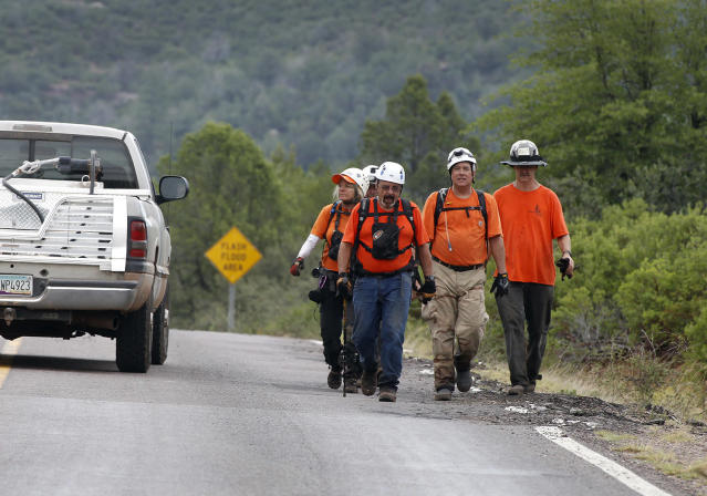 <p>Members of the Tonto Rim Search and Rescue team walk back to the Gila County Sheriff's Office mobile command center after searching for victims of a flash flood along the banks of the East Verde River on Sunday, July 16, 2017, in Payson, Ariz. (AP Photo/Ralph Freso) </p>