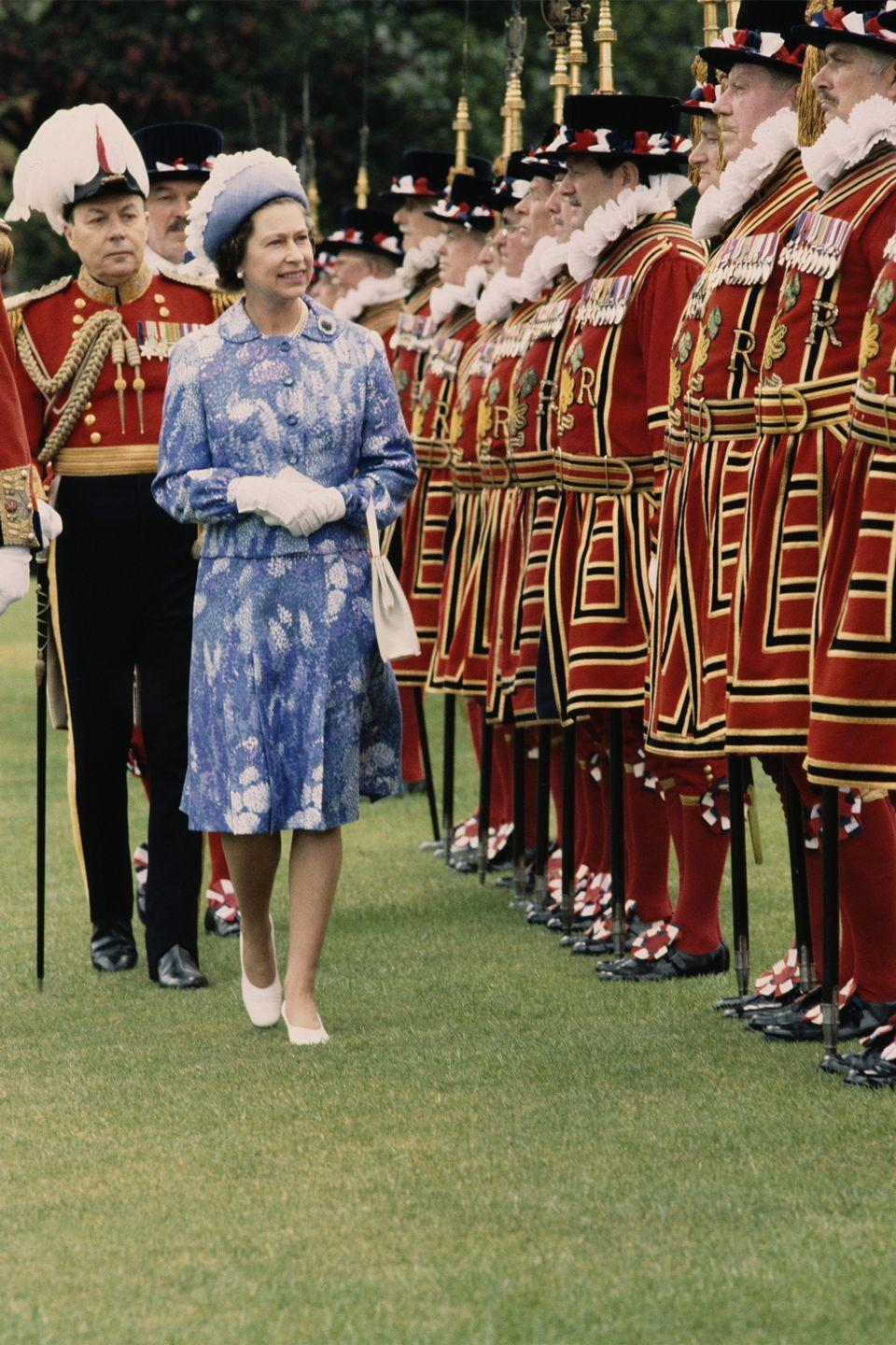 <p>Dressed in a blue and white blazer and skirt, Elizabeth inspects the royal bodyguard in London.</p>
