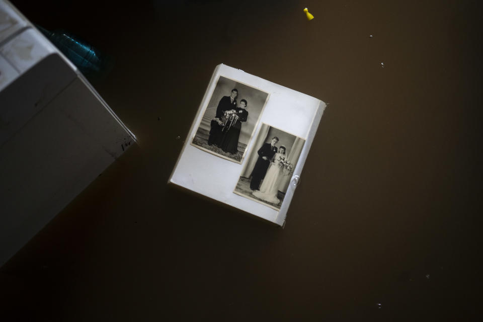 A view of wedding photos floating in water in a flooded basement of a home, in the town of Brommelen, Netherlands, Saturday, July 17, 2021. In the southern Dutch province of Limburg, which also has been hit hard by flooding, troops piled sandbags to strengthen a 1.1-kilometer (0.7 mile) stretch of dike along the Maas River, and police helped evacuate low-lying neighborhoods. (AP Photo/Bram Janssen)