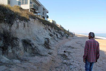 Walter Coker, a surfer, photographer and small business owner, surveys erosion under homes along the Atlantic Ocean beach north of St. Augustine, Florida, February 10, 2014. REUTERS/Duff Wilson