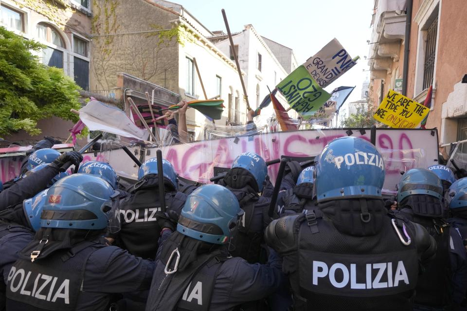 Demonstrators push their placards against a line of Italian Policemen in riot gears during a protest against the G20 Economy and Finance ministers and Central bank governors' meeting in Venice, Italy, Saturday, July 10, 2021. (AP Photo/Luca Bruno)