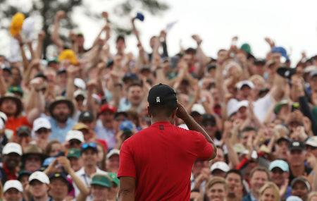 Golf - Masters - Augusta National Golf Club - Augusta, Georgia, U.S. - April 14, 2019. Spectators applaud as Tiger Woods of the U.S. celebrates on the 18th hole to win the 2019 Masters. REUTERS/Jonathan Ernst