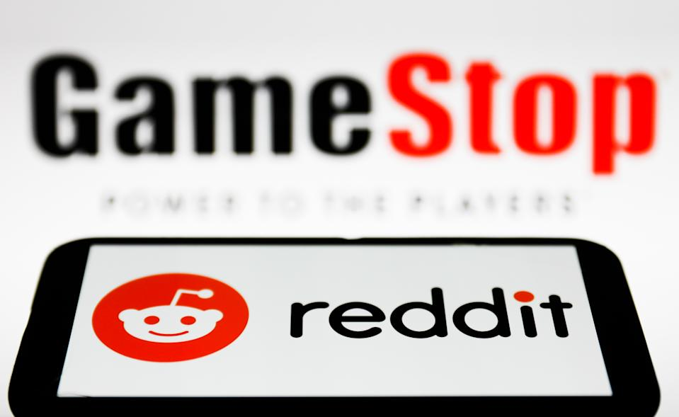 Reddit logo displayed on a phone screen and GameStop logo in the background are seen in this illustration photo taken in Poland on February 1, 2021. (Photo illustration by Jakub Porzycki/NurPhoto via Getty Images)