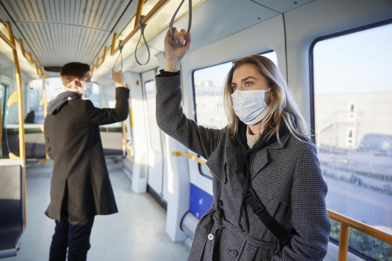 Young woman inside train, wearing a virus protective face mask