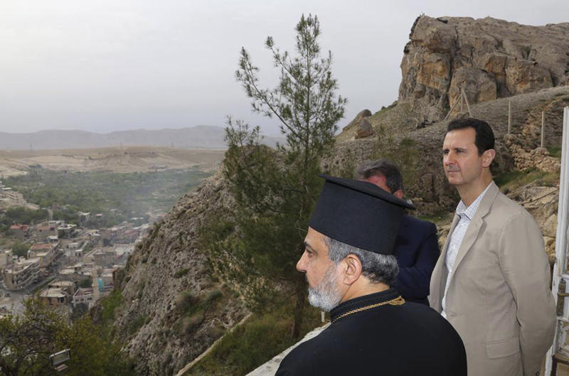"In this photo released by the Syrian official news agency SANA, Syrian President Bashar Assad, right, tours the Christian village of Maaloula, near Damascus, Syria, Sunday April, 20, 2014. Assad visited a historic Christian village his forces recently captured from rebels, state media said, as the country's Greek Orthodox Patriarch vowed that Christians in the war-ravaged country ""will not submit and yield"" to extremists. The rebels, including fighters from the al-Qaida-affiliated Nusra Front, took Maaloula several times late last year. (AP Photo/SANA)"