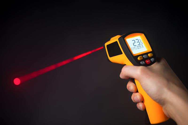 infrared laser thermometer in hand with red beam (Photo: nikkytok via Getty Images)