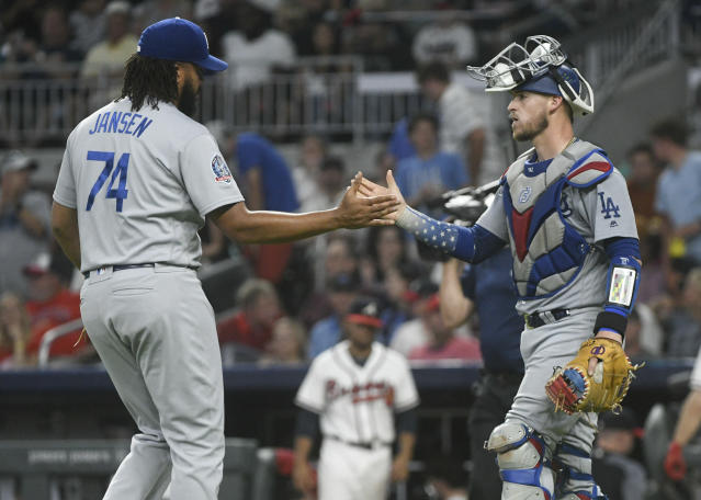 Los Angeles Dodgers pitcher Kenley Jansen (74) and catcher Yasmani Grandal congratulate each other after a baseball game against the Atlanta Braves, Friday, July 27, 2018, in Atlanta. (AP Photo/John Amis)
