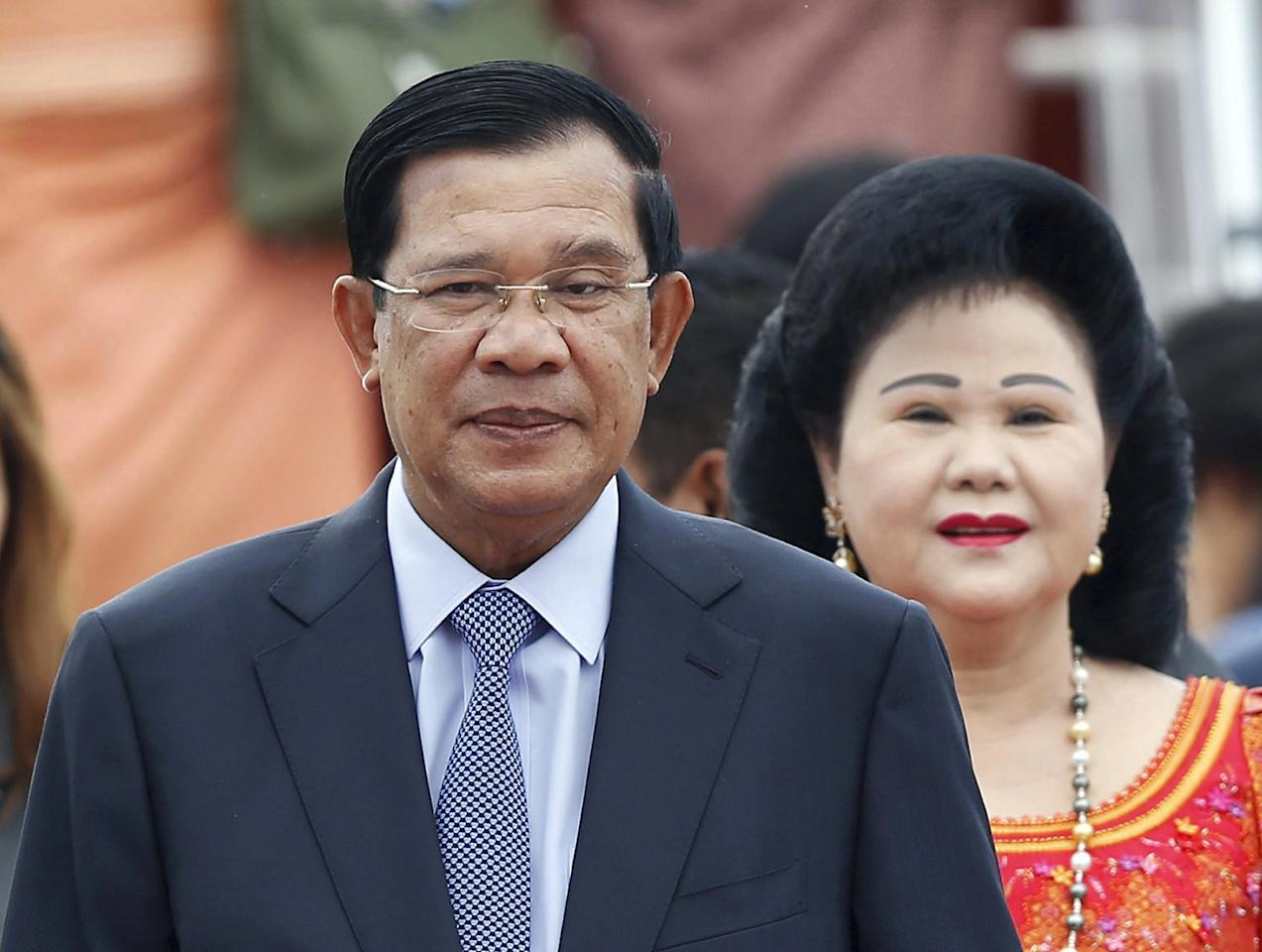 RETRANSMISSION WITH CORRECT SLUG - FILE - In this Nov. 20, 2015 file photo, Cambodia's Prime Minister Hun Sen and his wife Bun Rany arrive for the 27th Association of Southeast Asian Nations (ASEAN) summit, in Sepang, Malaysia. An extensive network of businesses controlled by the family of Cambodia's longtime leader sustains and is sustained by his authoritarian rule, making foreign investment in the country risky, says a report issued Thursday, July 7, 2016 by the research and advocacy group Global Witness. (AP Photo/Lai Seng Sin, File)