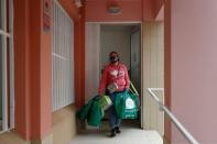 Carla Lacera leaves Reefood Food Bank after collecting food goods, during the coronavirus disease (COVID-19) pandemic in Faro