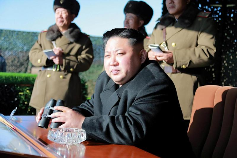 North Korean president Kim Jong-Un uses binoculars to watch a mock military drill. (REUTERS)