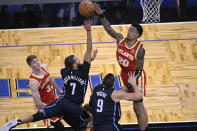 Orlando Magic guard Michael Carter-Williams (7) goes up for a shot between Atlanta Hawks guard Kevin Huerter (3) and forward John Collins (20) during the second half of an NBA basketball game Wednesday, March 3, 2021, in Orlando, Fla. (AP Photo/Phelan M. Ebenhack)