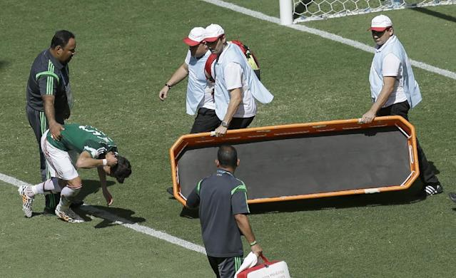 Mexico's Hector Moreno is helped off the field during the World Cup round of 16 soccer match between the Netherlands and Mexico at the Arena Castelao in Fortaleza, Brazil, Sunday, June 29, 2014. (AP Photo/Themba Hadebe)