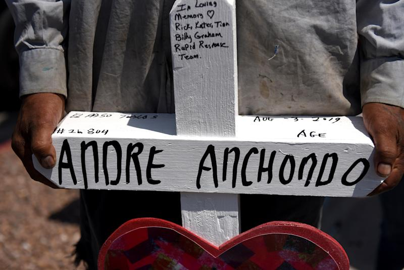 A man carries a cross, representing one of the victims Andre Anchondo, to a growing memorial site two days after a mass shooting at a Walmart store in El Paso, Texas, U.S. August 5, 2019. REUTERS/Callaghan O'Hare