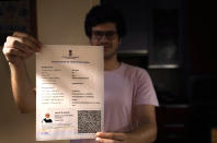 A boy displays his Covishield COVID-19 vaccination certificate in New Delhi, India, Wednesday, Sept. 22, 2021. Travelers and authorities from India and many African countries are furious — and confused — about Britain's new COVID-19 travel rules, calling them discriminatory. Covishield was added to the U.K.'s list of approved vaccines for travelers on Wednesday, but the group of approved public health bodies remained unchanged — meaning the practical effect of the move is limited. Outrage over Covishield was particularly pointed in India, where the vast majority of people have been vaccinated with the shot. (AP Photo/Manish Swarup)