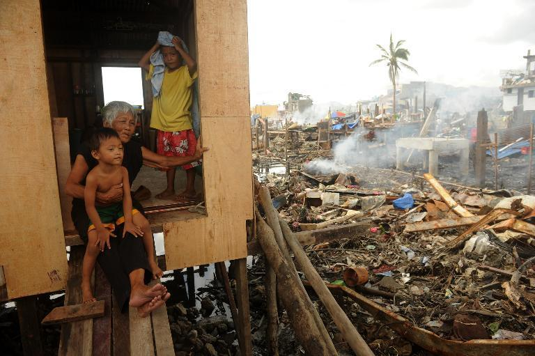 Trinidad Genario, 81, sits inside her newly constructed house with her grandchildren, among debris of destroyed houses in Tacloban, Leyte province on December 7, 2013