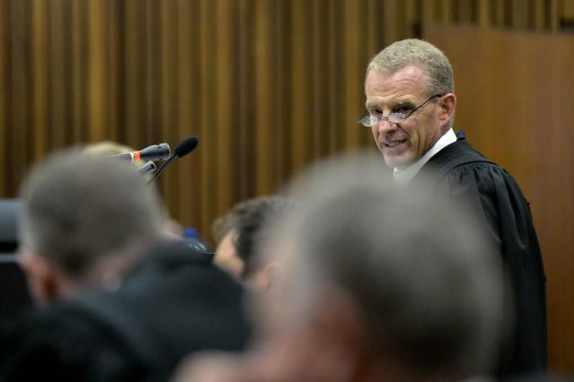 "State prosecutor Gerrie Nel reads out the charge sheet during the trial of Olympic and Paralympic track star Oscar Pistorius at the North Gauteng High Court in Pretoria March 3, 2014. ""Blade Runner"" Pistorius pleaded not guilty on Monday to murdering his girlfriend at the start of a trial with massive media cover that could see one of global sports' most admired role models go to jail for life. REUTERS/Herman Verwey/Pool (SOUTH AFRICA - Tags: SPORT ATHLETICS CRIME LAW)"