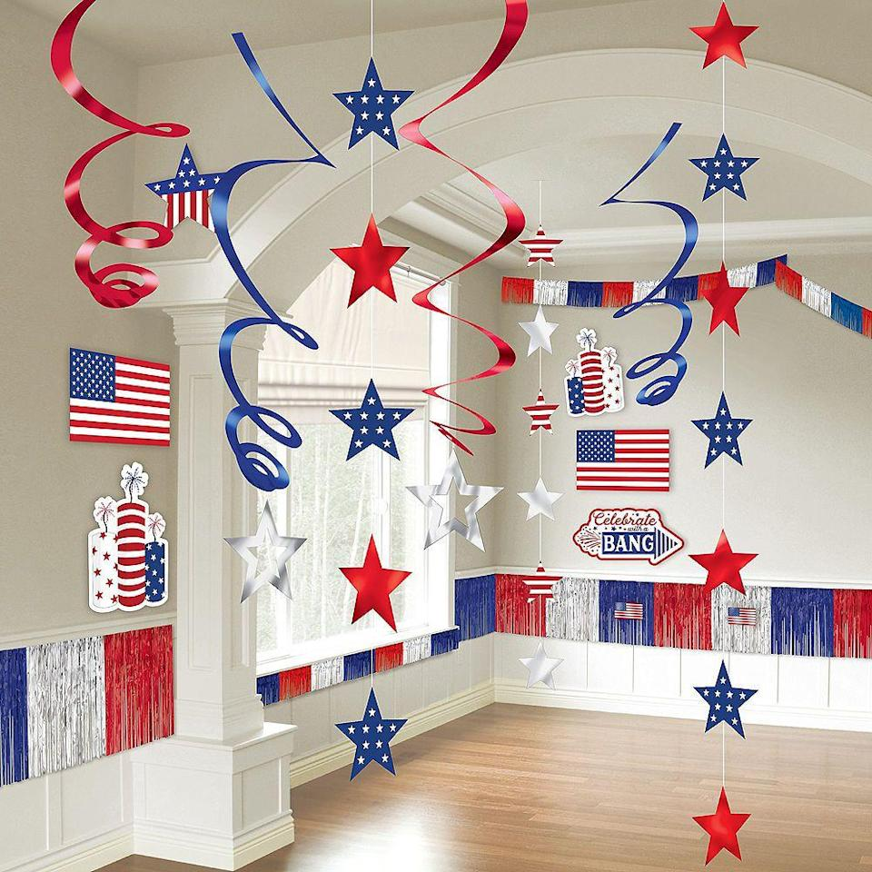 """<p>partycity.com</p><p><strong>$14.99</strong></p><p><a href=""""https://go.redirectingat.com?id=74968X1596630&url=https%3A%2F%2Fwww.partycity.com%2Fpatriotic-navy-and-red-room-decorating-kit-21pc-871798.html%3Fcgid%3D4th-of-july-decorations&sref=https%3A%2F%2Fwww.womansday.com%2Fhome%2Fdecorating%2Fg2441%2Ffourth-of-july-decorations%2F"""" rel=""""nofollow noopener"""" target=""""_blank"""" data-ylk=""""slk:Shop Now"""" class=""""link rapid-noclick-resp"""">Shop Now</a></p><p>This 21-piece kit includes paper cutouts, twisted streamers, and metallic fringe. </p>"""