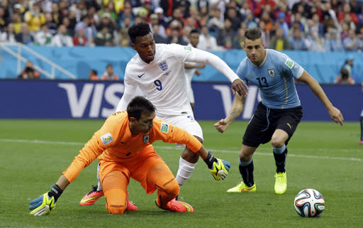 England's Daniel Sturridge, centre, battles for the ball with Uruguay's goalkeeper Fernando Muslera and Uruguay's Cristian Rodriguez during the group D World Cup soccer match between Uruguay and England at the Itaquerao Stadium in Sao Paulo, Brazil, Thursday, June 19, 2014. (AP Photo/Matt Dunham)