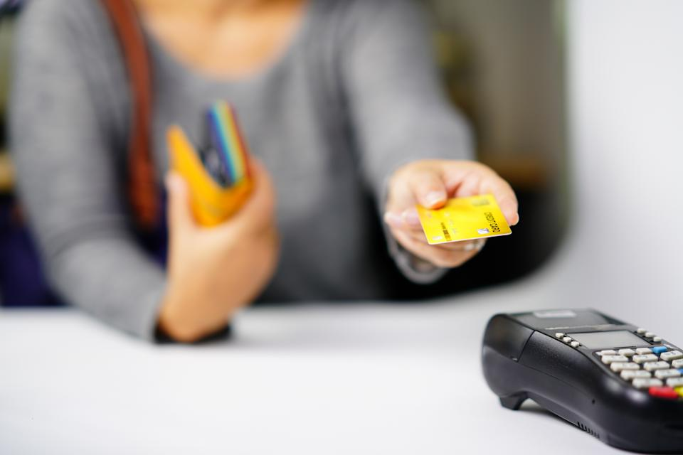 Woman using the credit card at the Shopping Mall spread payments for products and services,