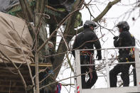 A protester, left, in a treetop camp films two officials approaching on a cherry picker in an encampment in Euston Square Gardens in central London, Wednesday Jan. 27, 2021. Protesters against a high-speed rail link between London and the north of England said Wednesday that some of them have been evicted from a park in the capital after they dug tunnels and set up a makeshift camp. (Aaron Chown/PA via AP)