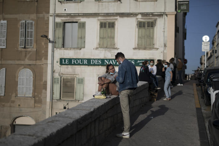 "Residents gather for drinks outdoors before curfew in Marseille, southern France, Friday, April 2, 2021. With France now Europe's latest virus danger zone, Macron on Wednesday ordered temporary school closures nationwide and new travel restrictions. But he resisted calls for a strict lockdown, instead sticking to his ""third way"" strategy that seeks a route between freedom and confinement to keep both infections and a restless populace under control until mass vaccinations take over. (AP Photo/Daniel Cole)"