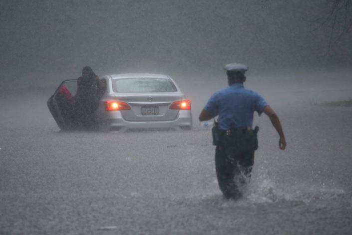 A Philadelphia police officer rushes to help a stranded motorist during Tropical Storm Isaias on Aug. 4. The storm spawned tornadoes and dumped rain during an inland march up the East Coast after making landfall as a hurricane along the North Carolina coast. It was NOAA's ninth-named storm so far this year, an unusually high number. (Photo: Associated Press)