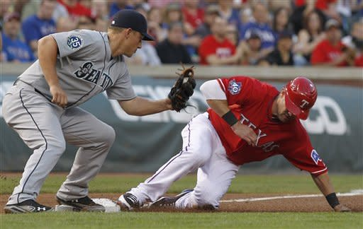Texas Rangers' Michael Young (10) slides safely into third base against Seattle Mariners third baseman Kyle Seager during the second inning of a baseball game Tuesday, April 10, 2012, in Arlington, Texas. Young advanced from second on a wild pitch. (AP Photo/LM Otero)