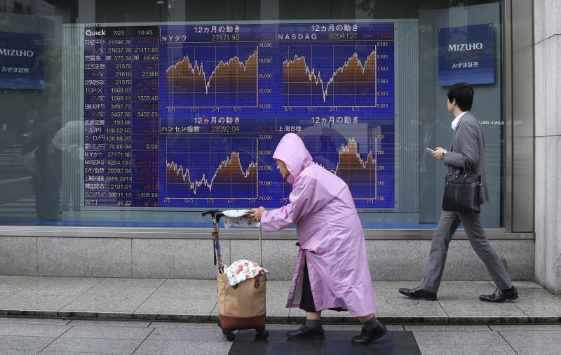 People walk by an electronic stock board of a securities firm in Tokyo, Tuesday, July 23, 2019. Asian stock markets rose on Tuesday on optimism over possible new U.S.-China talks despite rising Middle East tensions. (AP Photo/Koji Sasahara)