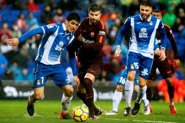 Barcelona's Spanish defender Gerard Pique (C) vies with Espanyol's Spanish forward Gerard Moreno (L) during the Spanish league football match between RCD Espanyol and FC Barcelona