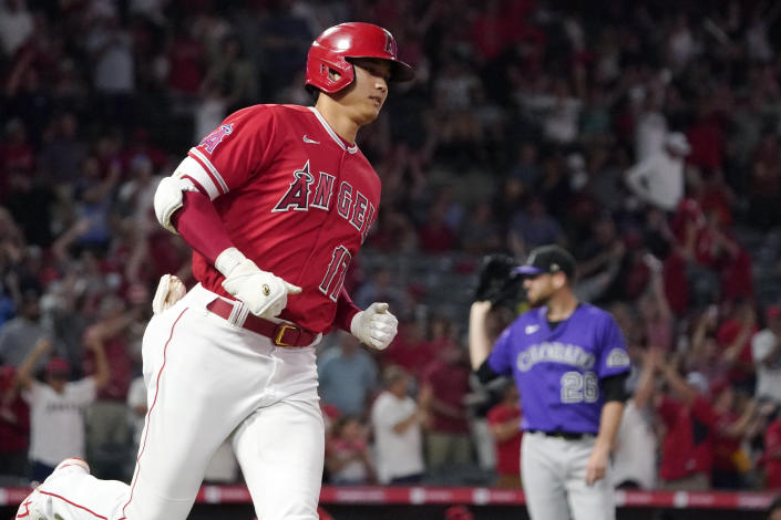 Los Angeles Angels' Shohei Ohtani, left, rounds first after hitting a two-run home run as Colorado Rockies starting pitcher Austin Gomber waits for another ball during the sixth inning of a baseball game Tuesday, July 27, 2021, in Anaheim, Calif. (AP Photo/Mark J. Terrill)