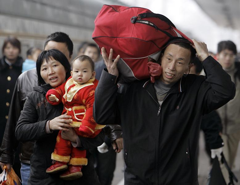 """FILE - In this Feb. 4, 2008 file photo, passengers walk to a train the Guangzhou railway station in Guangzhou, China as tens of millions of travelers scramble to board trains and buses to return home for this month's Lunar New Year holiday. Visit your parents. That's an order. So says China, whose national legislature on Friday, Dec. 28, 2012 amended its law on the elderly to require that adult children visit their aged parents """"often"""" - or risk being sued by them. (AP Photo/Kin Cheung, File)"""
