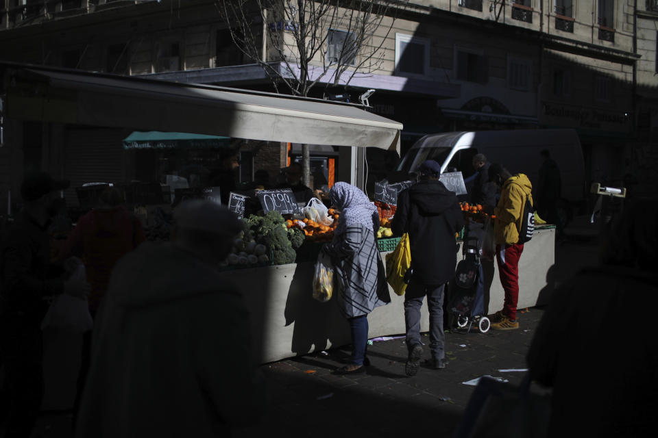"A woman shops at a street market in Marseille, southern France, Wednesday, Feb. 10, 2021. More than three dozen police officers descended on a small private school in Paris, blocked students inside their classrooms, took photos everywhere, even inside the refrigerator, and grilled the school director in her office. The dragnet sweeps schools, shops, clubs or mosques to rout out ""radicalization."" (AP Photo/Daniel Cole)"
