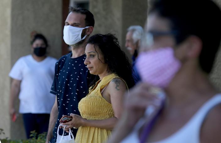 Neighbors look on outside the Reseda apartment.