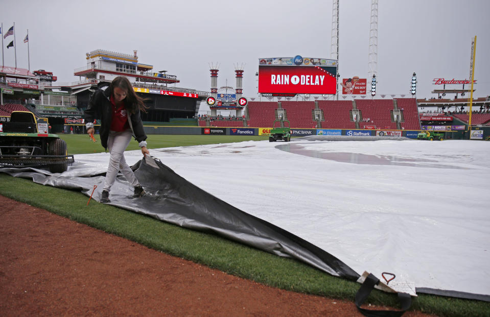A member of the grounds crew covers the field in the rain before the start of a baseball game between the Cincinnati Reds and the Pittsburgh Pirates, Wednesday, May 29, 2019, in Cincinnati. (AP Photo/Gary Landers)