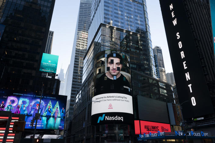 Brian Chesky, CEO of Airbnb, is shown on an electronic screen,, center, at the Nasdaq MarketSite, Thursday, Dec. 10, 2020, in New York. The San Francisco-based online vacation rental company holds its IPO Thursday. (AP Photo/Mark Lennihan)