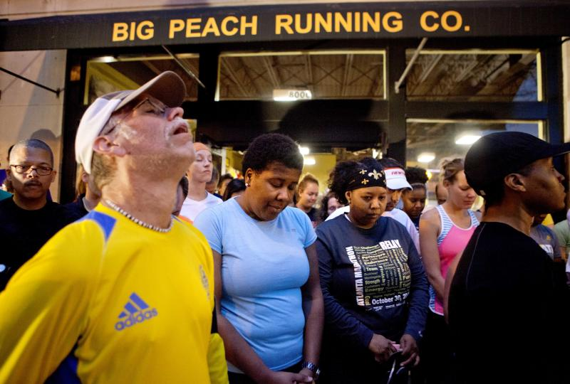 Runners observe a moment of silence before the start of an organized memorial run to show solidarity with victims of the Boston Marathon bombing, Tuesday, April 16, 2013, in Atlanta. The explosions Monday afternoon killed at least three people and injured at least 100 others. (AP Photo/David Goldman)