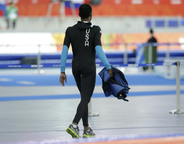 Shani Davis of the U.S. walks holding his jacket after competing in the men's speedskating team pursuit quarterfinals at the Adler Arena Skating Center during the 2014 Winter Olympics in Sochi, Russia, Friday, Feb. 21, 2014. (AP Photo/Matt Dunham)