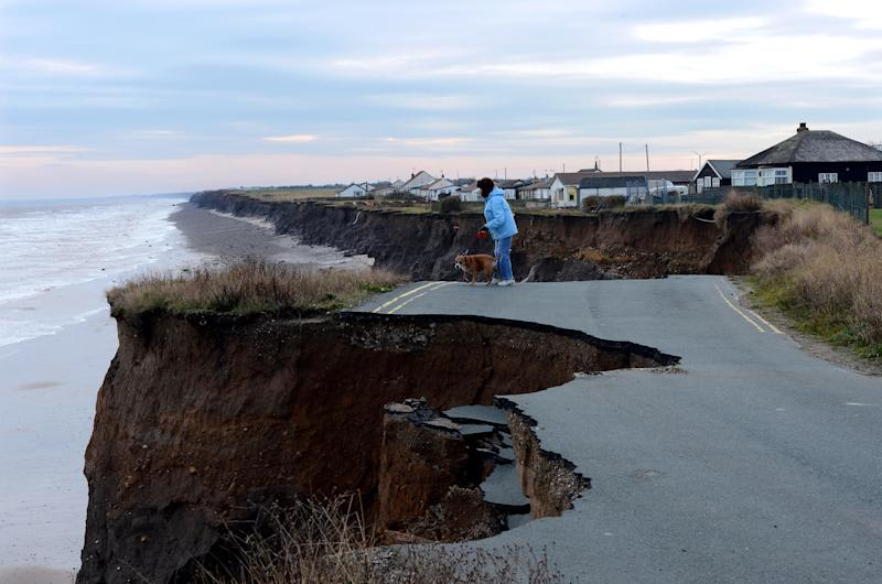 A woman looks over the eroded coastline (Picture: PA)